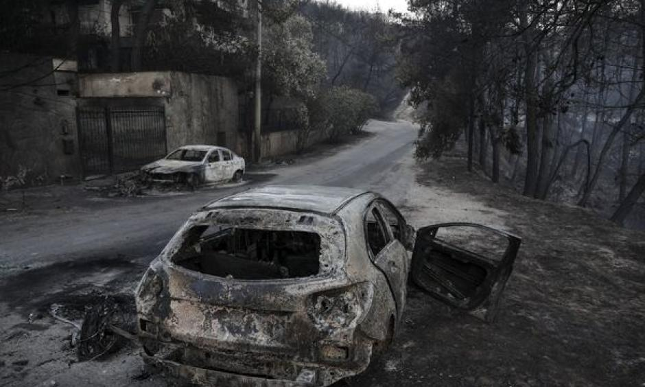 Burnt automobile line the streets following a wildfire east of Athens, on July 25. Credit: Yorgos Karahalis, Bloomberg