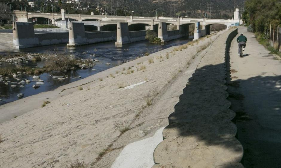 A cyclist rides along recently installed temporary flood control walls along the L.A. River in Los Angeles Friday, Feb. 12, 2016. Ten days with record heat and no rain have Californians worrying about the drought again. Photo: Damian Dovarganes, AP