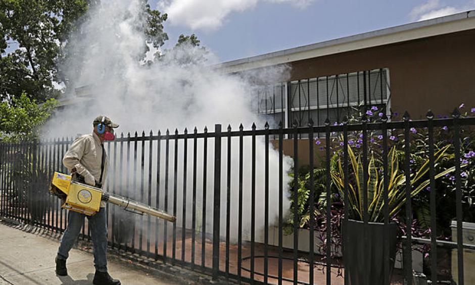 A Miami-Dade County mosquito control worker sprays around a home in the Wynwood area of Miami on Monday, Aug. 1, 2016. Photo: Alan Diaz