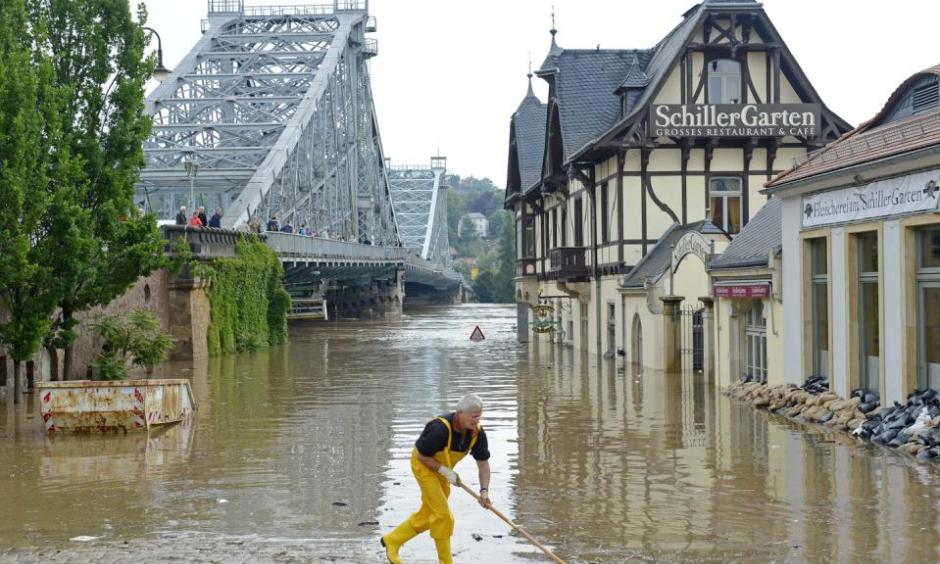 A helper cleans the bank of river Elbe in front of the historical bridge Blaues Wunder (Blue Miracle), left, in Dresden, eastern Germany, Thursday, June 6, 2013. Photo: Jens Meyer, AP