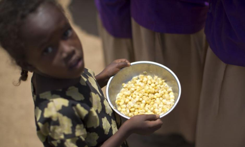A child holds a bowl of food given out during a food distribution in the drought-affected village of Bandarero, near Moyale town on the Ethiopian border, in northern Kenya, March 3, 2017. Photo: Voice of America via AP
