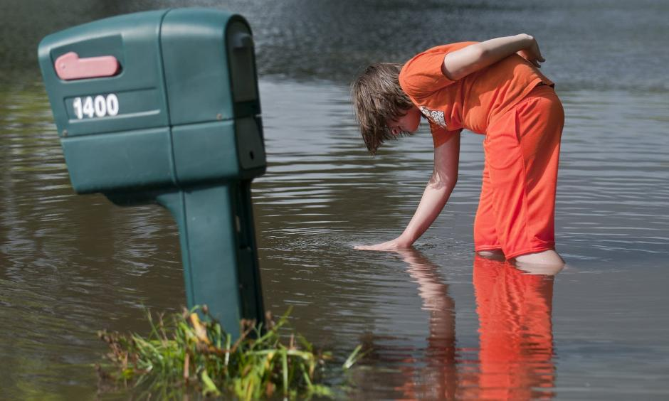 Logan Krevchuck, 14, puts his hand in a whirlpool as flood waters drained along Second Street Northwest in Waseca, Minn., Thursday. Photo: Jackson Forderer for MPR News