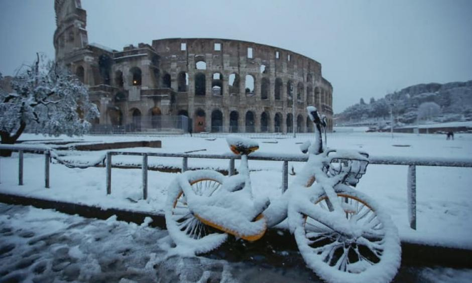 A bicycle is parked in front the ancient Colosseum during a snowfall in Rome. Photo: AP
