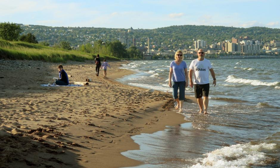 A couple walks along the Lake Superior shoreline at Park Point in Duluth. Photo: Dan Kraker | MPR News