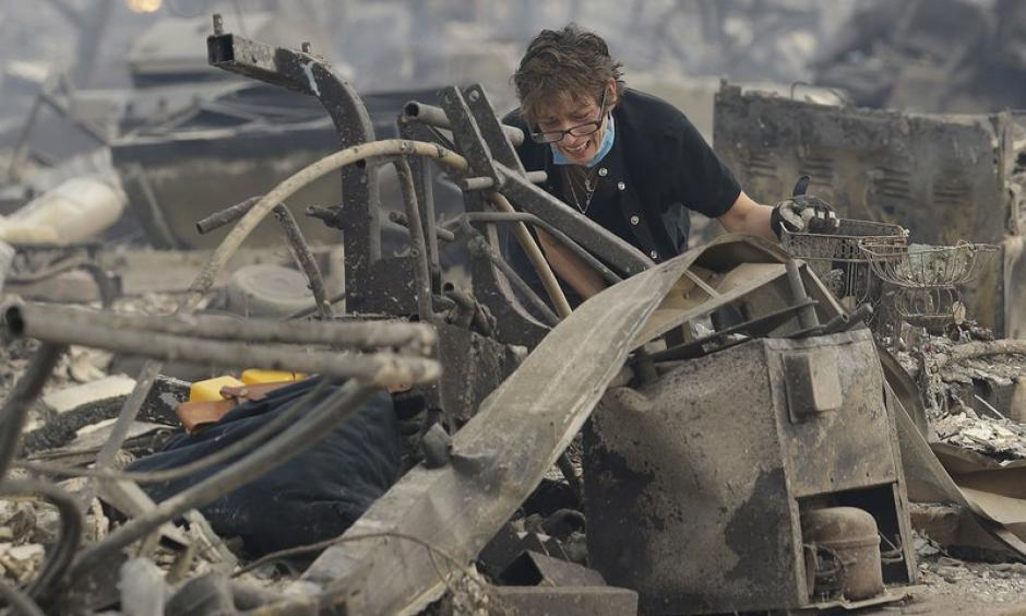 Kristine Pond reacts as she searches the remains of her family's home destroyed by wildfires in Santa Rosa, CA, Monday, October 9, 2017. Photo: Jeff Chiu, AP