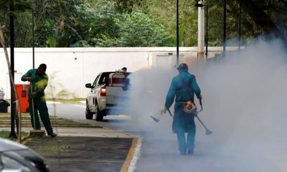 A truck sprays insecticide near grounds workers at Olympic media accommodations as part of preventative measures against the Zika virus and other mosquito-borne diseases in Rio de Janiero, Brazil. Photo: Chris Helgren, Reuters