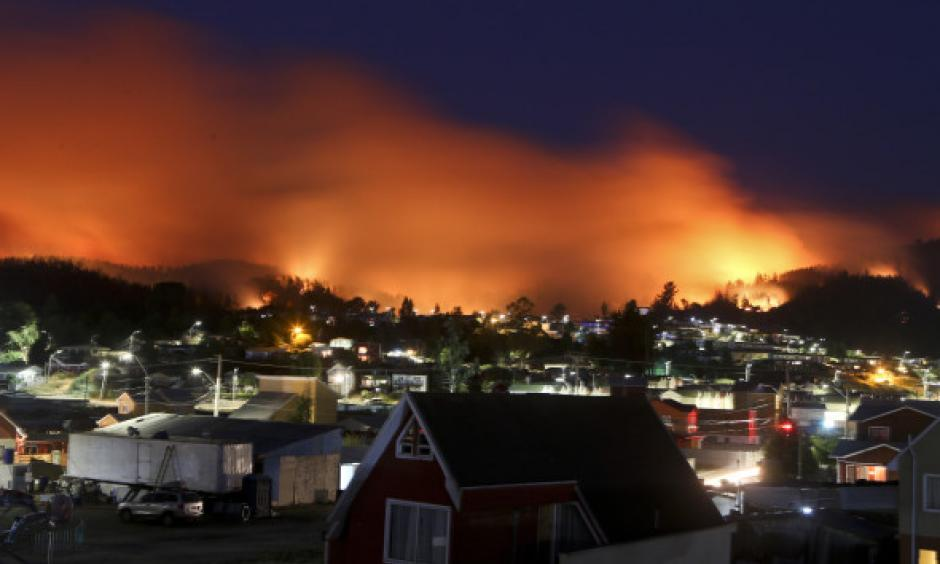 A wildfire approaches Chile's Dichato community, Monday, Jan. 30, 2017, where firefighters are working to keep the flames away from the estimated 800 homes. Families continue to be evacuated as firefighters battle the fires that are consuming a part of southern Chile. Photo: Esteban Felix, AP