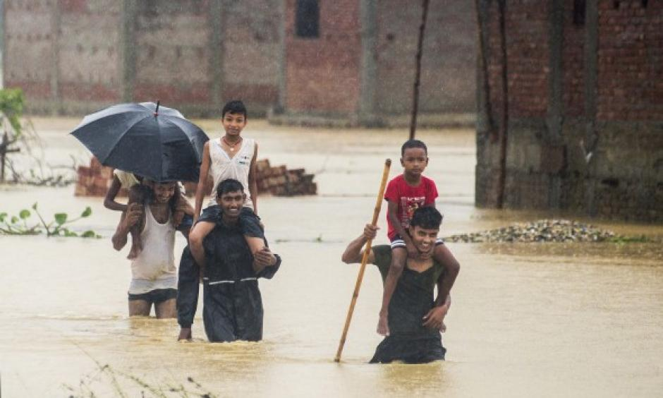 Nepalese men carry children on their shoulders as they wade through flood waters in village Ramgadhwa in Birgunj, Nepal, Sunday, Aug. 13, 2017. Photo: Manish Paudel, AP