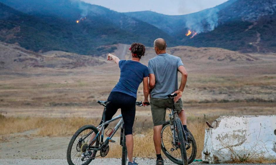 Two cyclists stopped to look at the Tenaja fire smoldering in the hills Thursday morning in Murrieta. A fast-moving fire erupted in hillside terrain near Murrieta on Wednesday night, quickly scorching almost 1,000 acres and prompting mandatory evacuation orders for multiple residential enclaves. Photo: Irfan Khan, LA Times
