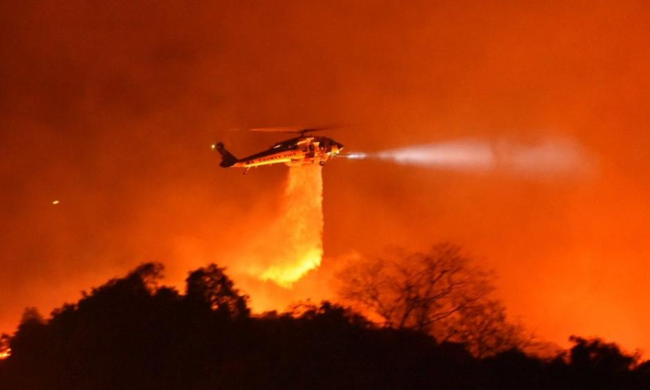 A Los Angeles County Firehawk copter makes a water drop on flames off CA Highway 154 north of Foothill Road. Credit: Mike Eliason / Santa Barbara County Fire