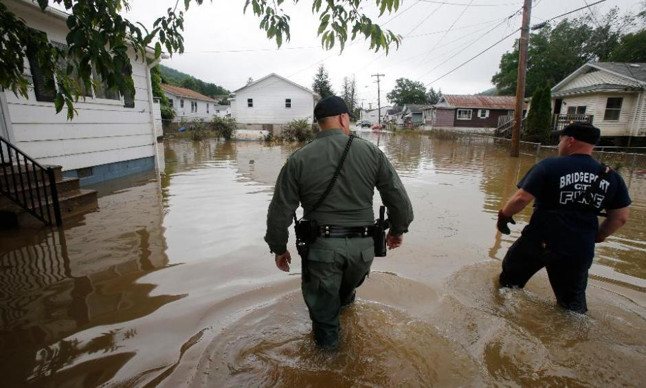 In this June 25, 2016, file photo, West Virginia State Trooper C.S. Hartman, left, and Bridgeport W. Va., fireman, Ryan Moran, wade through flooded streets as they search homes in Rainelle. A rainstorm that seemed no big deal at first turned into a catastrophe for the small town in West Virginia, trapping dozens of people whose screams would echo all night. Photo: Steve Helber, AP