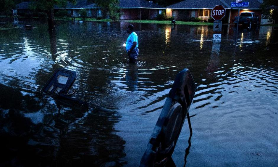Tracy Thornton walks to his house through a flooded neighborhood August 15, 2016 in Baton Rouge, Louisiana.Floods ravaged the US state of Louisiana. Photo: Brendan Smialowski, AFP, Getty Images