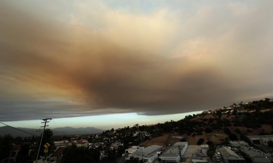Smoke from a nearby wildfire looms over Los Angeles on Friday, viewed from Monterey Park, Calif. Photo: Nick Ut/AP
