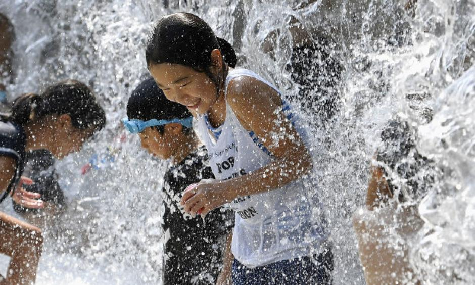 In this July 14, 2018 file photo, children play in a water fountain set up at a park in Tokyo during an extreme heat wave. (Kyodo)