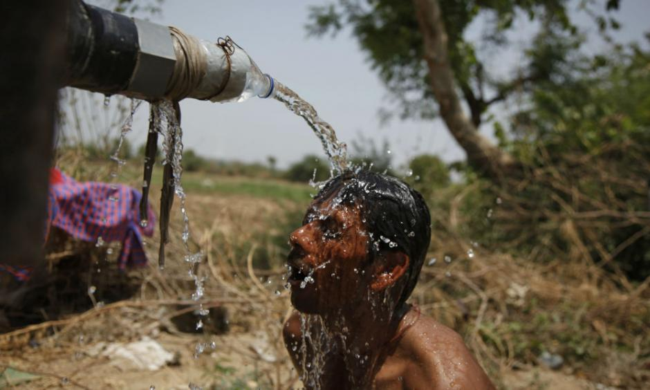 An Indian man takes bath under the tap of a water tanker on a hot day in Ahmadabad, India, Thursday, May 21, 2015. Photo: AP