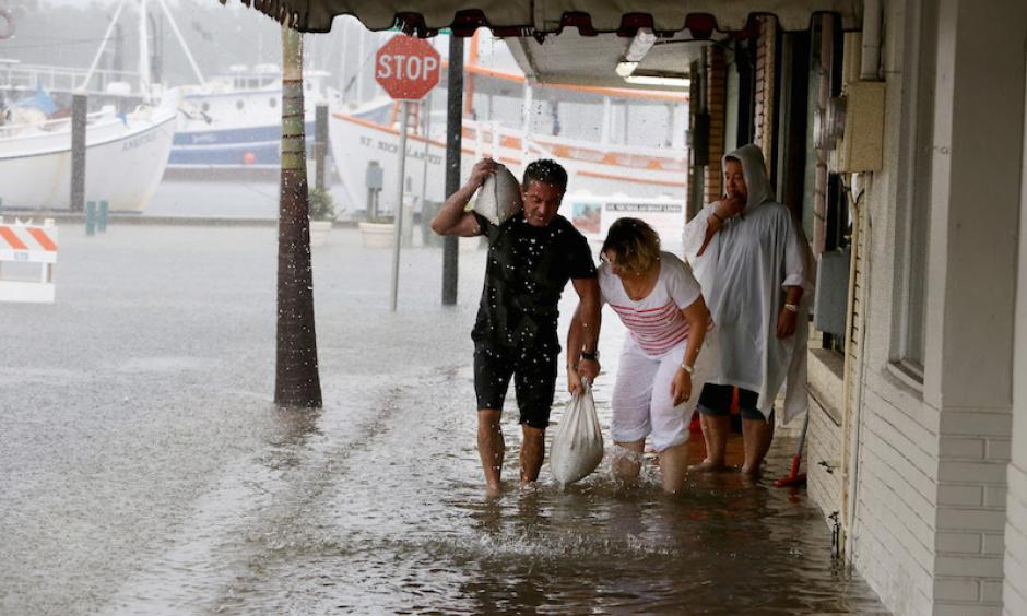 Angelo Memiakis, left, and Kelly Spiliotis work to deliver sandbags to the door jams of businesses along flooded Athens Street on Monday, June 6, 2016, in Tarpon Springs, FL, as Tropical Storm Colin barreled up the west coast of Florida. Photo: Douglas R. Clifford/The Tampa Bay Times via AP