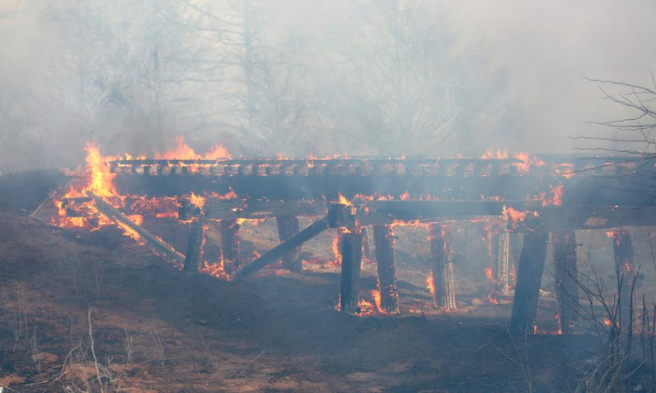 A old train trestle bridge burns near Lake City, KS, on Wednesday, March 23, 2016. The bridge was set afire by a large grass fire burning in Barber County, KS. Lake City is about 15 miles northwest of Medicine Lodge, where at least two homes were destroyed by fire. Photo: Travis Morisse, The Hutchinson News via AP