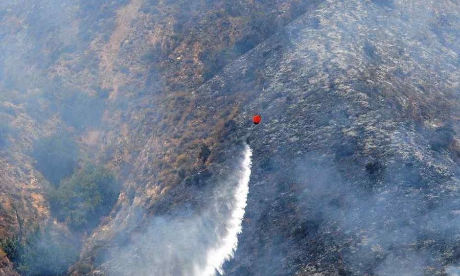 A helicopter makes a water drop on the Soberanes Fire as it burns on the west slope of Mount Manuel in Pfeiffer Big Sur State Park on Tuesday. Photo: Vern Fisher / Monterey Herald