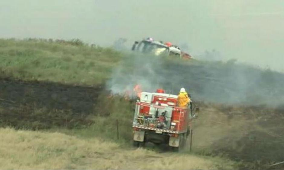 Crews work to contain a grass fire near the Hume Highway, Goulburn. (Image: 9News)