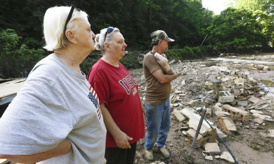 Emma Allen, center, and James Allen look at the remnants of their home after flooding damage with Pauline Stanley in Clendenin, W.Va., on Sunday. Photo: Marcus Constantino / Reuters