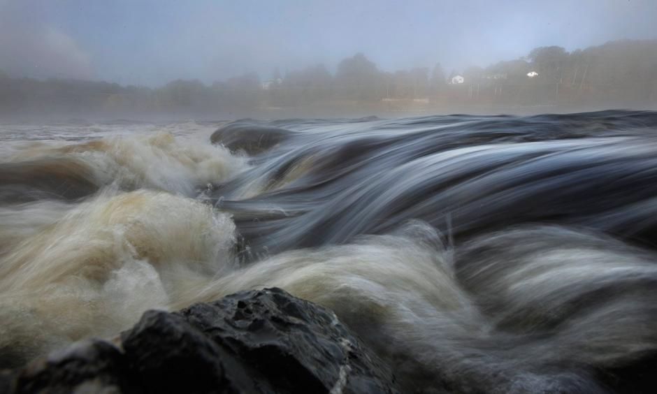 Swollen from recent rains, the Penobscot River flows through the area of the river where the Veazie Dam once stood. The dam, along with the Great Works Dam farther downstream, was removed two years ago in an effort to allow salmon easier passage to spawning grounds upriver from the dam. Photo: Gregory Rec, Staff Photographer