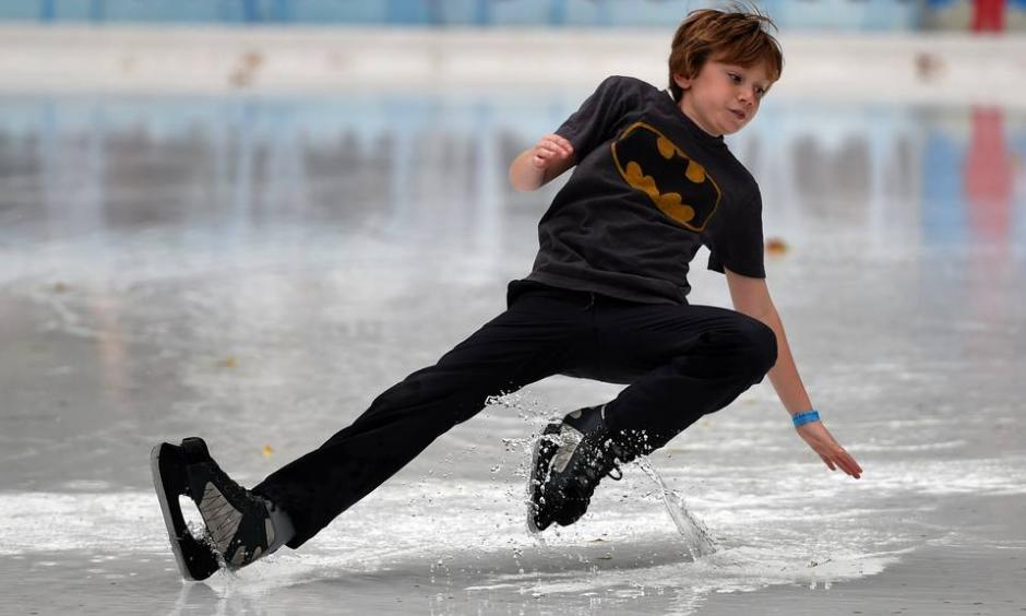 As New York City experienced an unseasonably warm month, a young skater slipped on a huge puddle of water from the melted ice at the Bryant Park rink. Photo: Timothy A. Clary, Agence France-Presse, Getty
