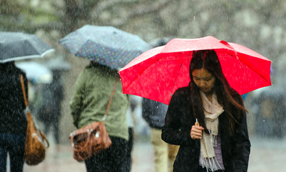 Passersby brave the heavy rains in California. Photo: Kevin Ho Nguyen