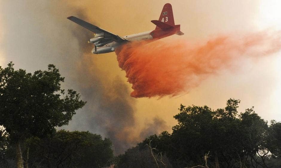 A plane drops a load of retardant on a wildfire north of Lompoc, California, Monday, June 29, 2015. Photo: Associated Press