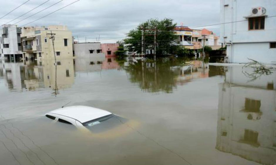 A car is submerged amidst water-logged houses in a rain-hit area of Chennai. (AFP)