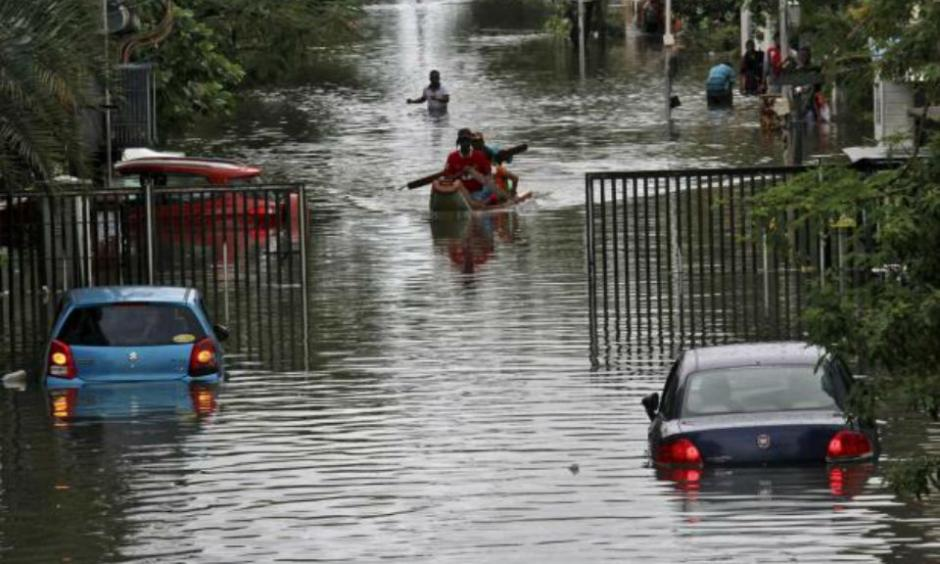 People travel on a boat as they move to safer places through a flooded road in Chennai, India, December 2, 2015. REUTERS/STRINGER