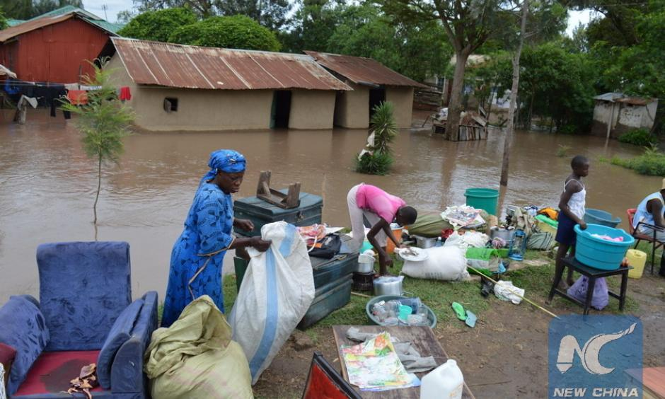 Residents of River Nyando salvage their property after the river burst its banks and caused floods in Kisumu, western Kenya, Nov. 17, 2015. Local residents were displaced and crops destroyed after the heavy rains. Photo: Simbi Kusimba, Xinhua