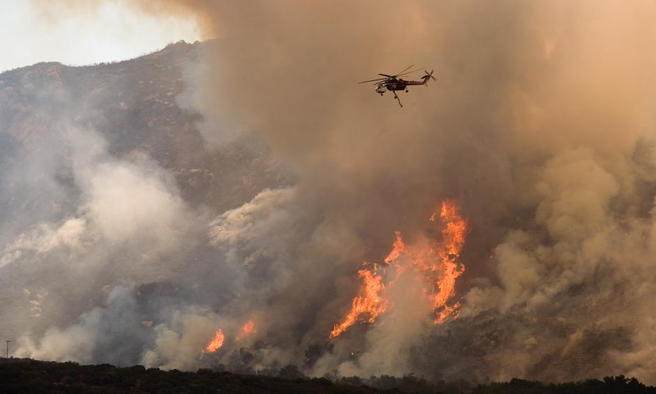 A helicopter drops water on the wildfire in California. Photo: FEMA