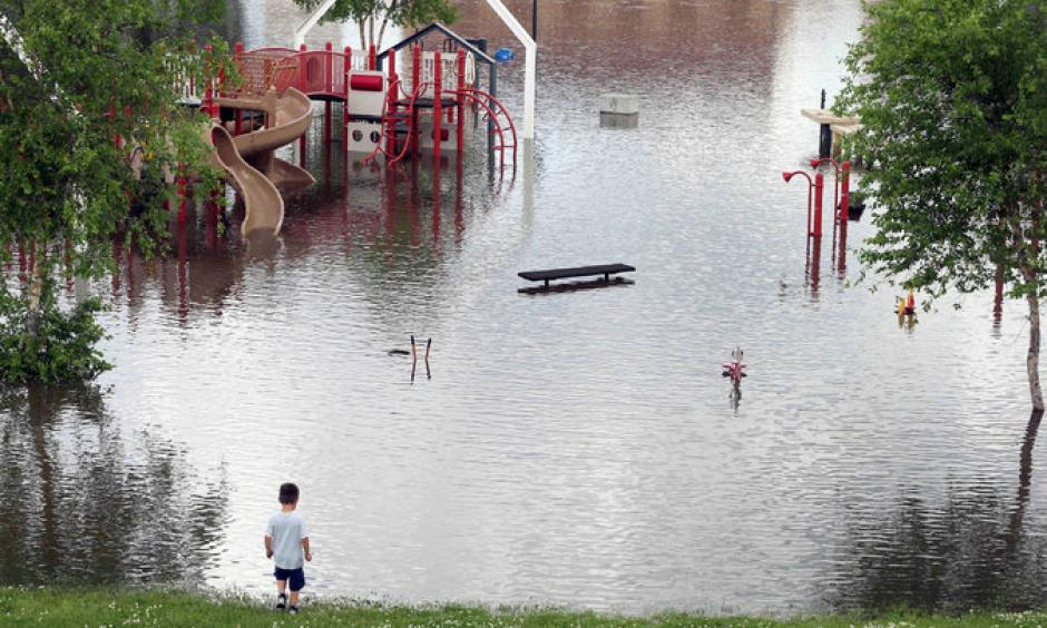 The rising Mississippi River covered a playground and closed roads on Tuesday in St. Paul. Photo: Jim Mone, Associated Press