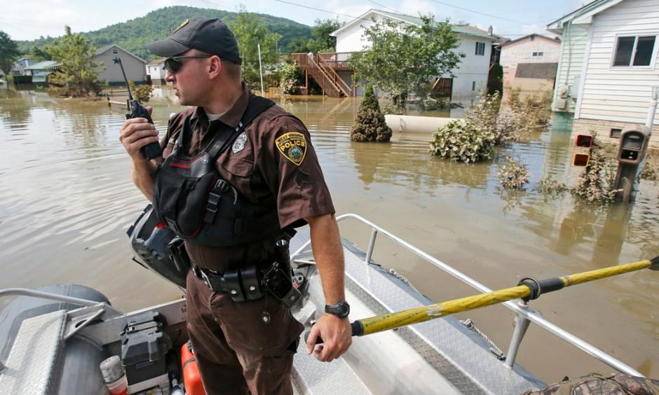 Lt. Dennis Feazell, of the West Virginia Department of Natural Resources, contacts his command center as he and a co-worker search flooded homes in Rainelle, W. Va., Saturday, June 25, 2016. Photo: AP