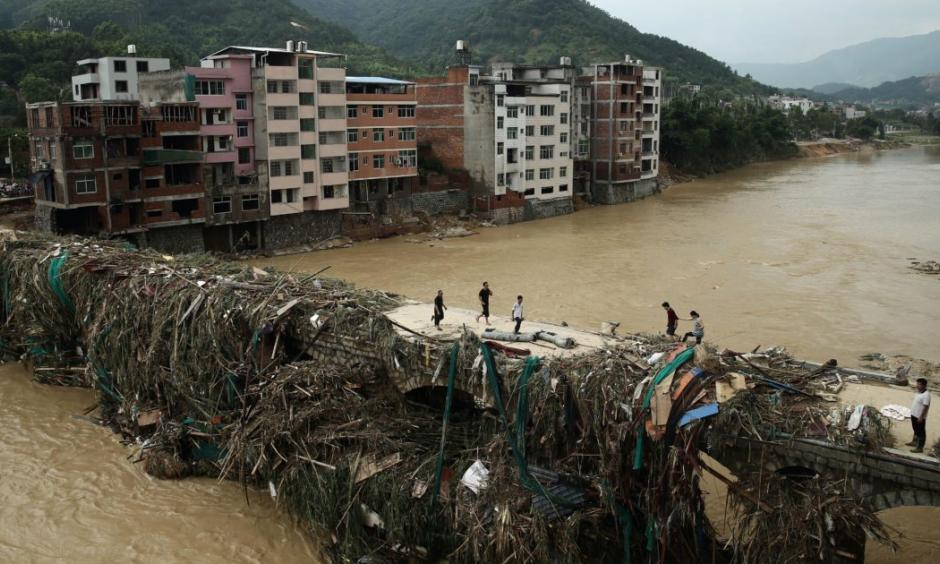 Residents gingerly walking over a bridge mounded with debris in Bandong Town in China's Fujian province. Photo: STR / AFP / Getty Images