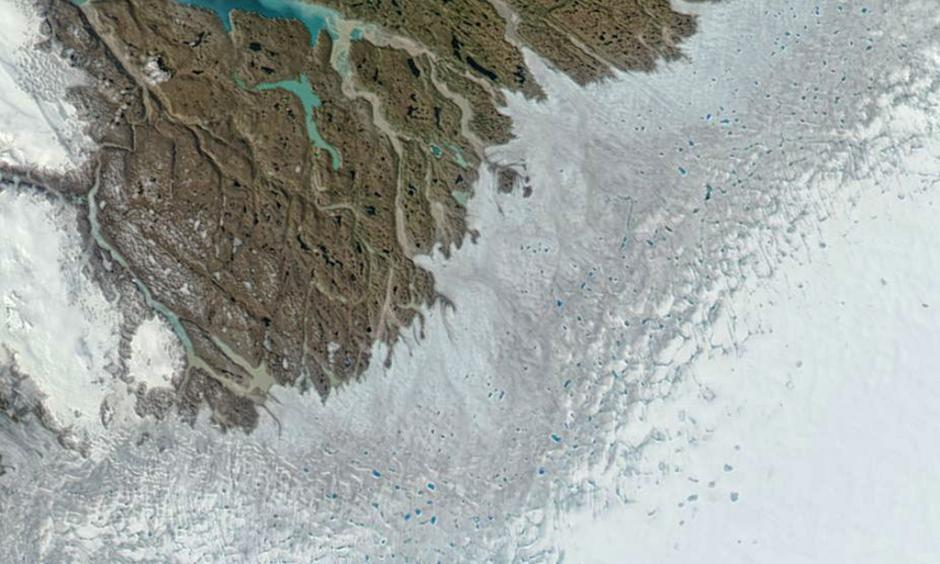 Numerous melt ponds are visible in this image of Greenland's southwest coast, captured by NASA's Aqua satellite on June 12, 2016. The grayish-blue band also is indicative of melting at the surface. Photo: NASA EOSDIS