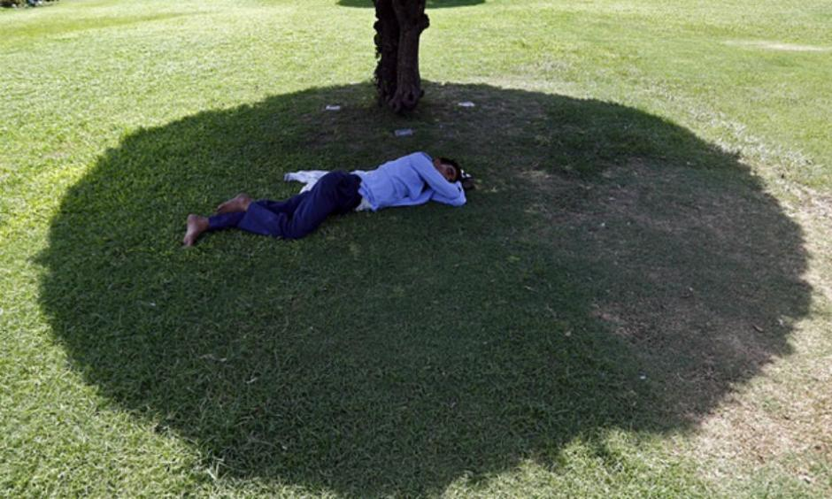 A man sleeps under the shade of a tree during a May 2015 heat wave in New Delhi, India. Photo: Anindito Mukherjee, Reuters