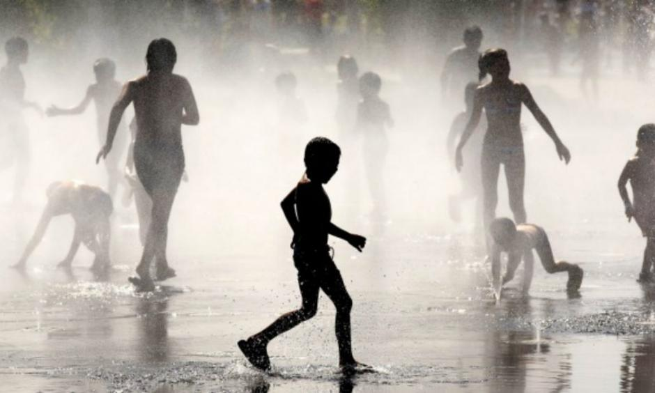 Children cool off under a fountain in Madrid in July this year. Photo: Pablo Blazquez Dominguez