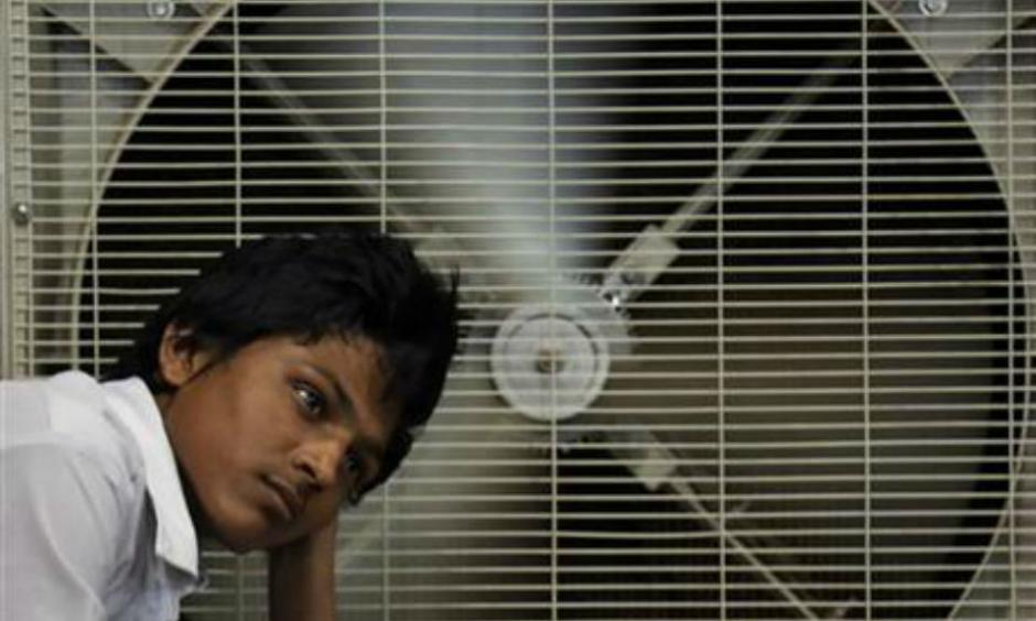 In this May 31, 2015 file photo, an Indian man rests in front of an air cooler to cool. Photo: AP