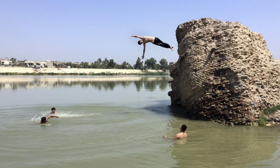 Iraqis jump off the ruins of an old building into the Tigris River to beat the heat in Baghdad on Aug. 1. The temperature in Baghdad reached 117 degrees. Photo: Ali Abdul Hassan/AP