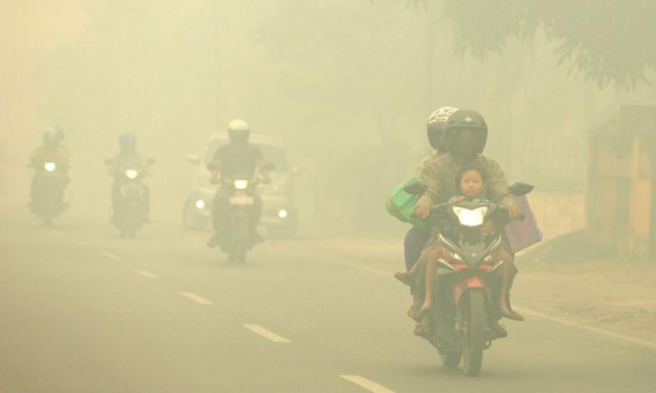 Motorists ride on a road as thick haze from forest fires shrouds the city in Palangkaraya, Central Borneo, Indonesia, on Tuesday, October 27, 2015. The haze has blanketed parts of western Indonesia for about two months and affected neighboring countries like Singapore, Malaysia and Thailand. Image credit: Associated Press.