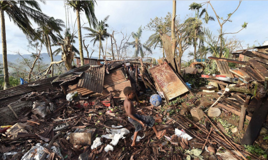 In Vanuatu's capital, Port Vila, a boy named Samuel kicked a ball through the ruins of his family's home as his father, Phillip, at back, picked through the debris on Monday. Image: Dave Hunt, AP
