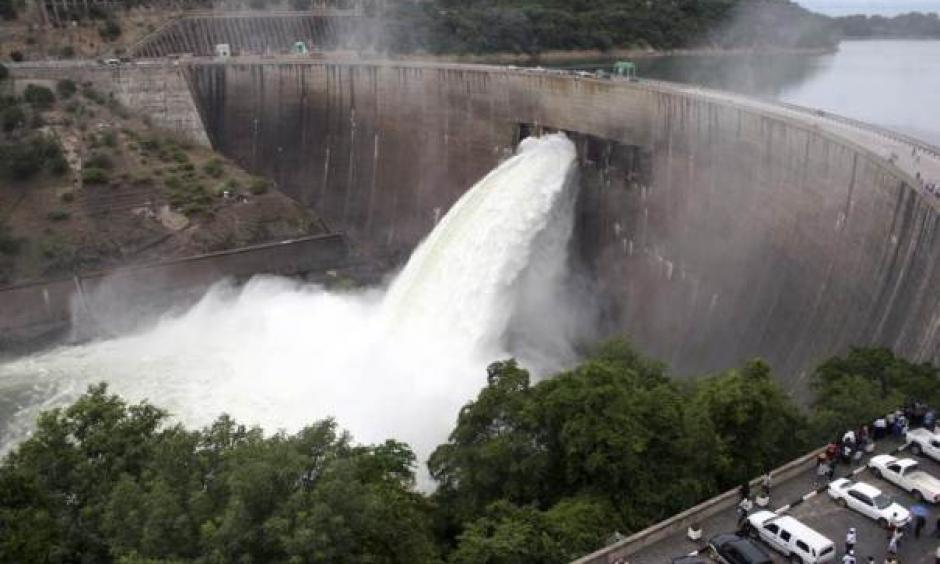 In this file 2008 photo, people watch as the spillway gates are opened at Kariba North Bank dam on Lake Kariba to reduce rising water levels as a measure to protect the dam. Photo: Mackson Wasamunu, Reuters