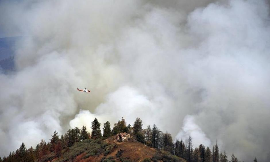 A United States Forest Service Cobra helicopter flies over the burn-out operation along McKenzie Ridge Saturday, September 19, 2015 near Kings Canyon National Park, Calif. ERIC PAUL ZAMORA