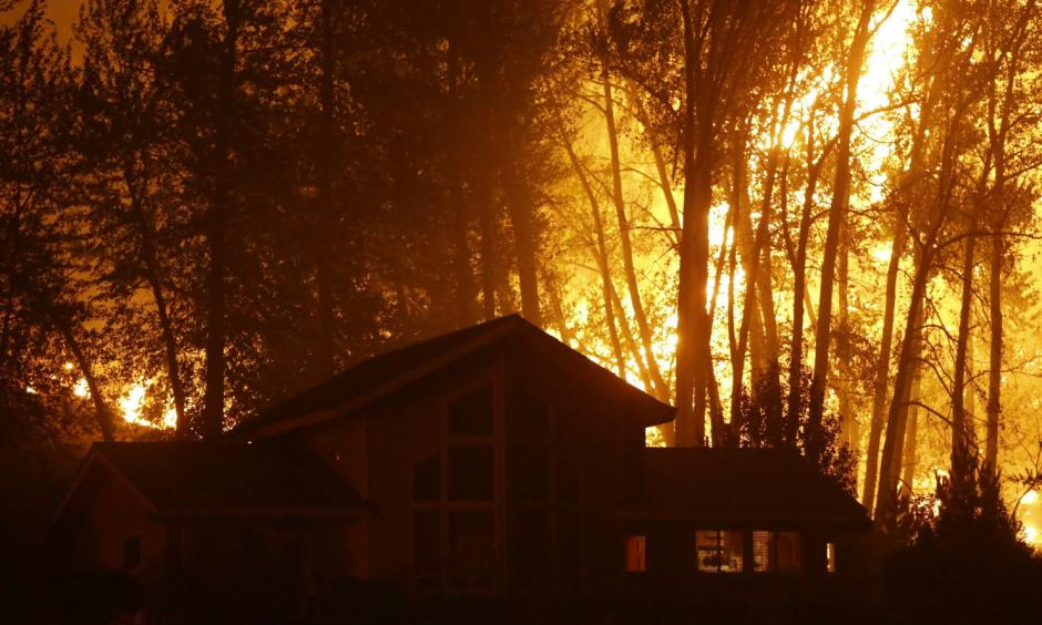 A wildfire burns behind a home in Twisp, Washington, in August. Authorities urged people in the town to evacuate because of the fast-moving blaze. (Ted S. Warren/AP)