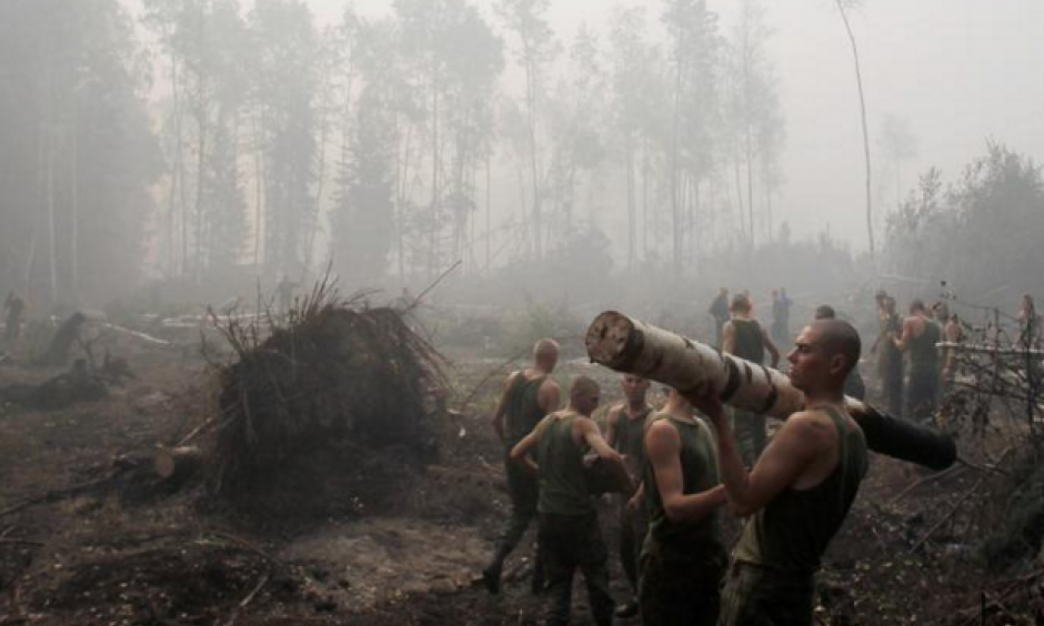 Russian service members haul away trees felled to hold wildfires at bay outside the town of Lukhovitsy on August 6. Photo: Denis Sinyakov, Reuters