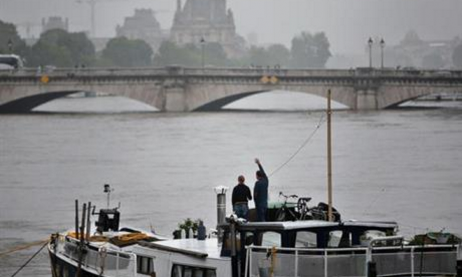 A man waves to somebody on a barge on the Seine river during floods, in Paris, Sunday, June 5, 2016. The riverside Grand Palais exhibition hall in Paris reopened Sunday as floodwaters slowly receded from the French capital, though risks remain for other regions. Photo: Thibault Camus, AP