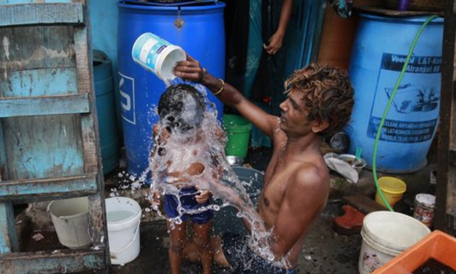 In this May 23, 2016 file photo, a man bathes his son on a hot afternoon in Mumbai, India. Federal scientists say Earth sizzled to its 13th straight month of record heat in May. Photo: Rafiq Maqbool, AP