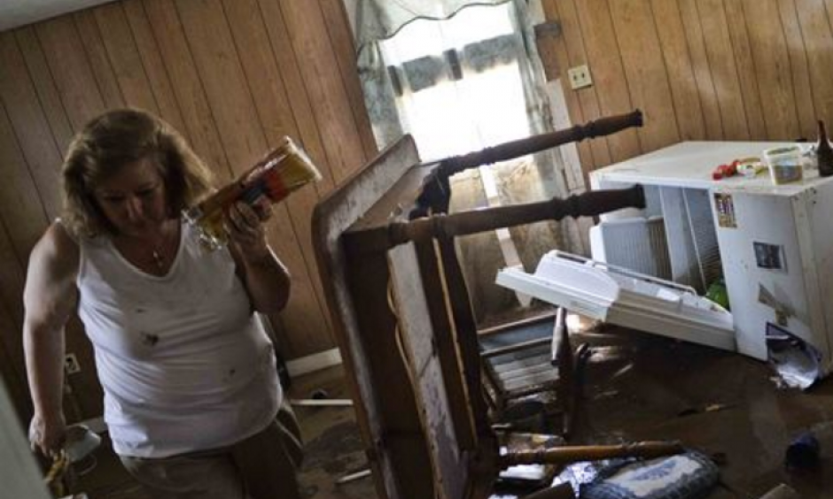 Theresa Havers helps clean out the kitchen of her son's home after flooding in Rainelle, W.Va., on June 26, 2016. Photo: Christian Tyler Randolph, Charleston Gazette-Mail, via AP