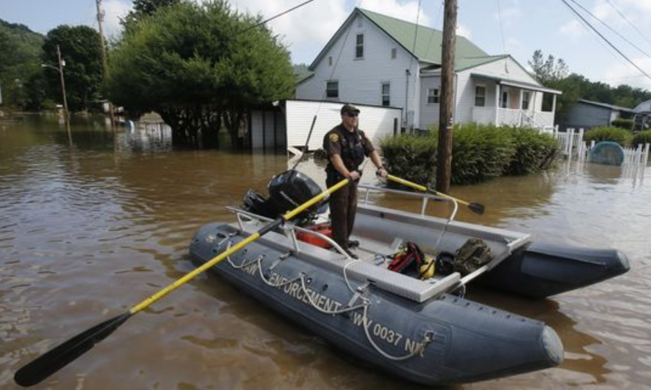 Lt. Dennis Feazell, of the West Virginia Department of Natural Resources, rows his boat as he and a co-worker search flooded homes in Rainelle, W. Va. on June 25, 2016. About 32,000 West Virginia homes and businesses remain without power Saturday after severe flooding hit the state. The West Virginia Division of Homeland Security and Emergency Management also said that more than 60 secondary roads in the state were closed. Photo: Steve Helber, AP